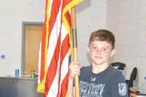 Sixth grader Gage Rice posts the American flag.
